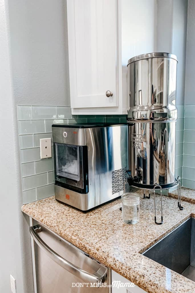 Berkey water filter on counter top near white cupboard