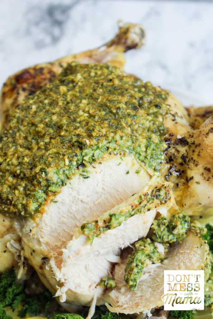 close up of cooked chicken covered in pesto