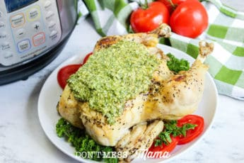 cooked whole chicken with pesto on a plate