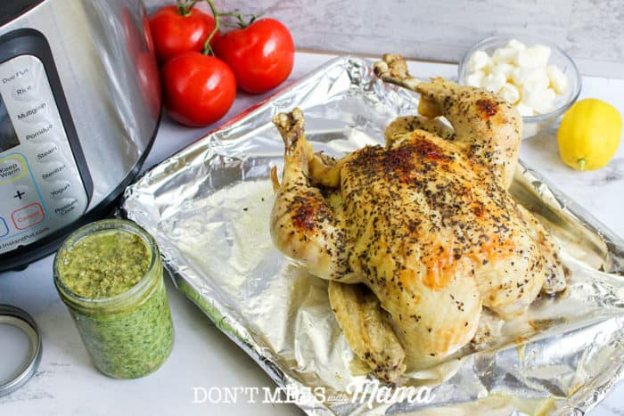 cooked whole chicken on tray with jar of pesto