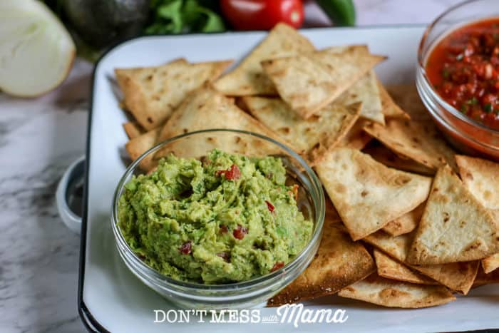 small bowl of homemade guacamole with tortillas on a plate