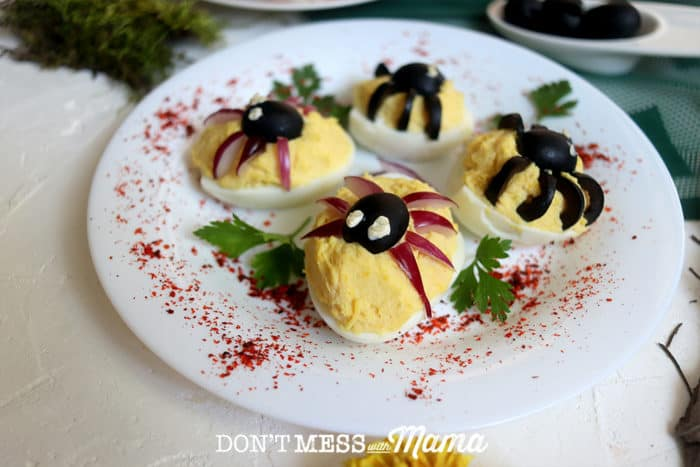 deviled eggs topped with olive spiders on a white plate